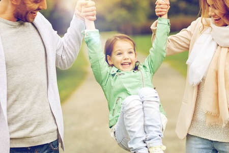 Foto de family, happiness, childhood and people concept - close up of happy mother, father and little girl walking in summer park and having fun - Imagen libre de derechos