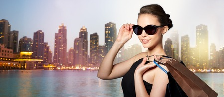 Photo pour sale, fashion, people and luxury concept - happy beautiful young woman in black sunglasses with shopping bags over dubai night city lights street background - image libre de droit
