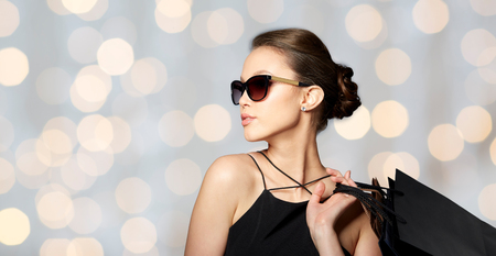 Foto de sale, fashion, people and luxury concept - happy beautiful young woman in black sunglasses with shopping bags over holidays lights background - Imagen libre de derechos