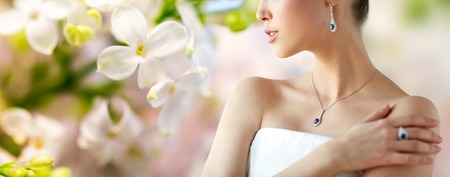 Photo pour beauty, jewelry, people and luxury concept - beautiful asian woman or bride with earring, finger ring and pendant over natural spring lilac blossom background - image libre de droit