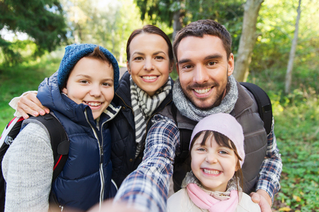 Photo for technology, travel, tourism, hike and people concept - happy family with backpacks taking selfie and hiking - Royalty Free Image