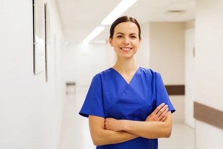 Foto de healthcare, profession, people and medicine concept - happy doctor or nurse at hospital corridor - Imagen libre de derechos
