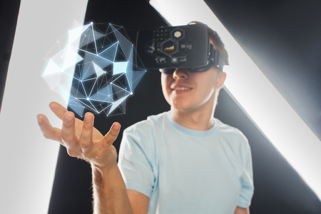 Foto de 3d technology, virtual reality, science and people concept - close up of happy young man with virtual reality headset or 3d glasses playing game and holding polygonal shape projection - Imagen libre de derechos