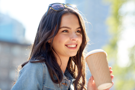 Photo for drinks and people concept - happy young woman or teenage girl drinking coffee from paper cup on city street - Royalty Free Image