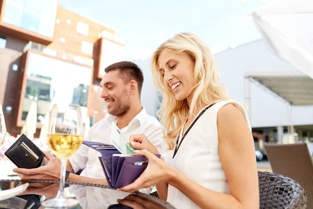 Foto de date, people, relations, payment and finances concept - happy couple with wallet and wine glasses paying bill at restaurant - Imagen libre de derechos