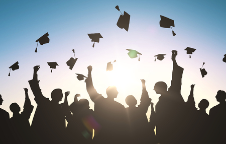 Photo for education, graduation and people concept - silhouettes of many happy students in gowns throwing mortarboards in air - Royalty Free Image