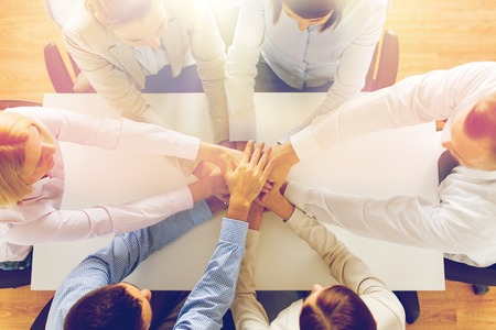Foto de business, people, cooperation and team work concept - close up of creative team sitting at table and holding hands on top of each other in office - Imagen libre de derechos