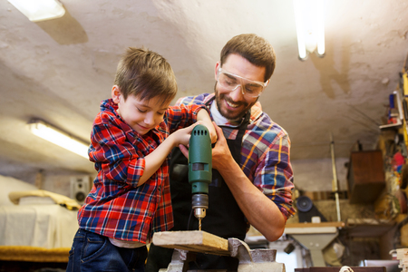 Photo for family, carpentry, woodwork and people concept - father and little son with drill perforating wood plank at workshop - Royalty Free Image