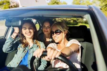 Photo pour summer vacation, holidays, travel, road trip and people concept - happy teenage girls or young women driving in car - image libre de droit