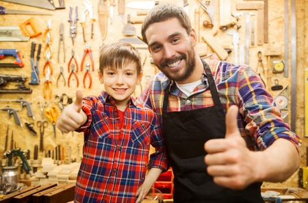 Photo for family, carpentry, woodwork, gesture and people concept - happy father and little son making thumbs up at workshop - Royalty Free Image