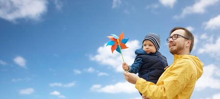 Photo for family, childhood, fatherhood, leisure and people concept - happy father and little son with pinwheel toy over blue sky and clouds background - Royalty Free Image