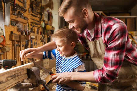 Photo for family, carpentry, woodwork and people concept - happy father and little son with rasp grinding wood plank at workshop - Royalty Free Image