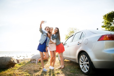 Photo pour summer vacation, holidays, travel, road trip and people concept - happy teenage girls or young women with smartphone taking selfie near car at seaside - image libre de droit