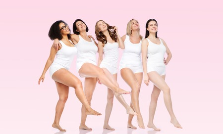 Photo for friendship, beauty, body positive and people concept - group of happy women different in white underwear over pink background - Royalty Free Image