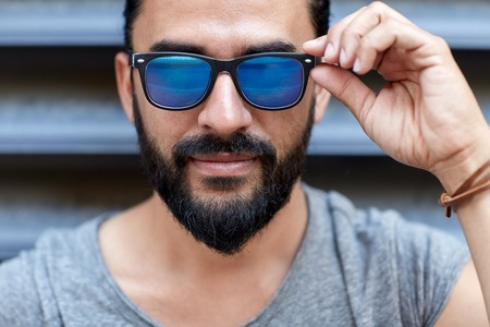 Photo for lifestyle, emotion, expression and people concept - happy smiling man with sunglasses and beard on city street - Royalty Free Image