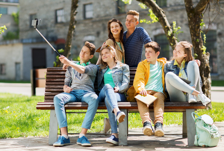 Foto de education, high school, technology and people concept - group of happy teenage students or friends taking selfie by smartphone and monopod - Imagen libre de derechos
