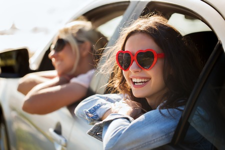 Photo pour summer holidays, valentines day, travel, road trip and people concept - happy teenage girls or young women heart shaped sunglasses in car at seaside - image libre de droit