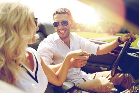 Foto de road trip, travel, dating, couple and people concept - happy man and woman driving in cabriolet car outdoors - Imagen libre de derechos