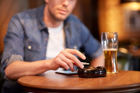 Foto per people, nicotine addiction and bad habits concept - close up of man drinking beer, smoking cigarette and shaking ashes to ashtray at bar or pub - Immagine Royalty Free