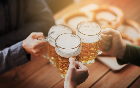 Foto de people, leisure and drinks concept - close up of hands clinking beer mugs at bar or pub - Imagen libre de derechos