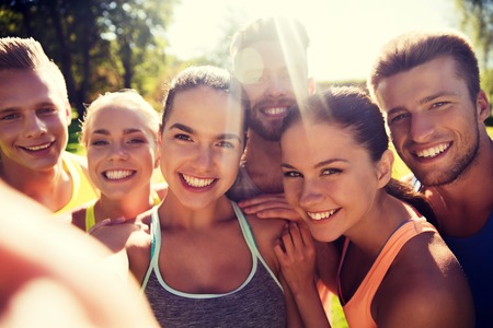 Foto de fitness, sport, friendship, technology and healthy lifestyle concept - group of happy teenage friends taking selfie with smartphone outdoors - Imagen libre de derechos