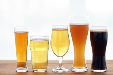 Photo for brewery, drinks and alcohol concept - close up of different beers in glasses on table - Royalty Free Image