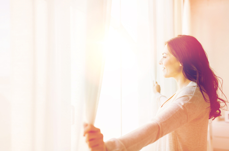Foto de people and hope concept - close up of happy woman opening window curtains - Imagen libre de derechos