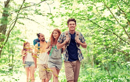 Foto de adventure, travel, tourism, hike and people concept - group of smiling friends walking with backpacks in woods - Imagen libre de derechos