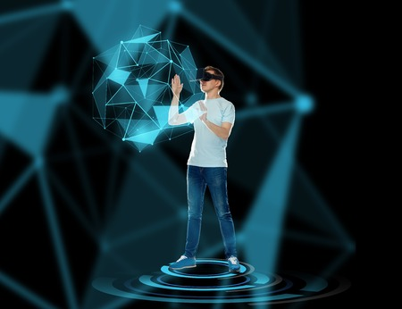 Foto de 3d technology, augmented reality, gaming, cyberspace and people concept - happy young man with virtual reality headset or 3d glasses playing game and touching low poly shape hologram - Imagen libre de derechos