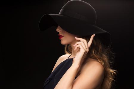 Foto de people, luxury and fashion concept - beautiful woman in black hat over dark background - Imagen libre de derechos