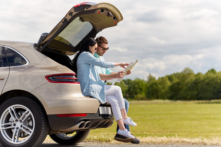 Photo pour leisure, road trip, travel and people concept - happy man and woman searching location on map sitting on trunk of hatchback car outdoors - image libre de droit