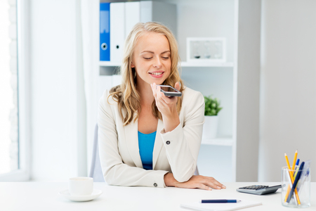 Photo for business, tecnology, communication and people concept - happy businesswoman drinking coffee and using voice command or recorder on smartphone at office - Royalty Free Image