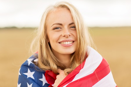 Photo pour country, patriotism, independence day and people concept - happy smiling young woman wrapped into national american flag on cereal field - image libre de droit