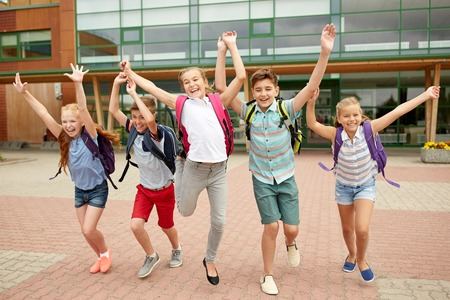 Foto de primary education, friendship, childhood and people concept - group of happy elementary school students with backpacks running and waving hands outdoors - Imagen libre de derechos