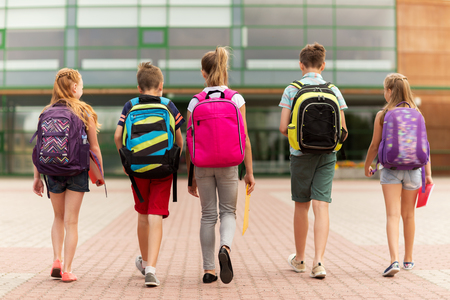 Photo for primary education, friendship, childhood and people concept - group of happy elementary school students with backpacks walking outdoors from back - Royalty Free Image