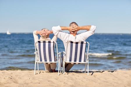 Photo pour family, age, travel, tourism and people concept - happy senior couple sitting on deck chairs on summer beach - image libre de droit