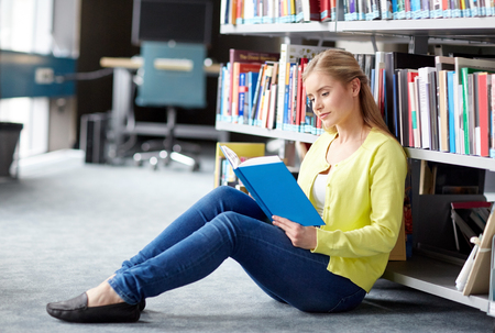 Foto de education, high school, university, learning and people concept - smiling student girl reading book sitting on floor at library - Imagen libre de derechos