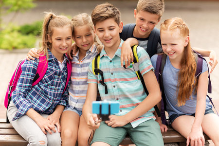Photo pour primary education, technology, friendship, childhood and people concept - group of happy school students with backpacks sitting on bench and taking picture by smartphone on selfie stick outdoors - image libre de droit