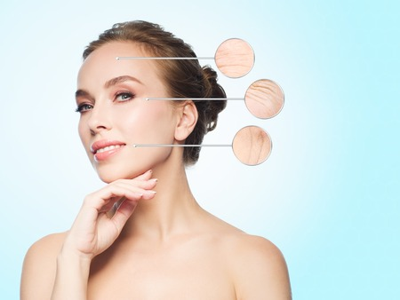 Foto de beauty, people, aging and skin concept - beautiful young woman touching her face over blue background - Imagen libre de derechos