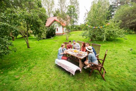 Foto de leisure, holidays, eating, people and food concept - happy friends having dinner at summer garden party - Imagen libre de derechos