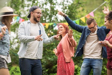 Photo pour leisure, holidays, fun and people concept - happy friends dancing at summer party in garden - image libre de droit