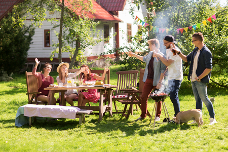Photo pour leisure, food, people, friendship and holidays concept - happy friends cooking meat on barbecue grill and drinking beer at summer outdoor party - image libre de droit