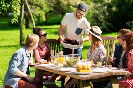 Photo for leisure, holidays, eating, people and food concept - happy friends having meat for dinner at summer garden party - Royalty Free Image