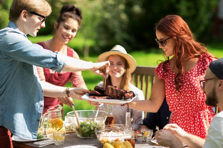 Photo pour leisure, holidays, eating, people and food concept - happy friends having meat for dinner at summer garden party - image libre de droit