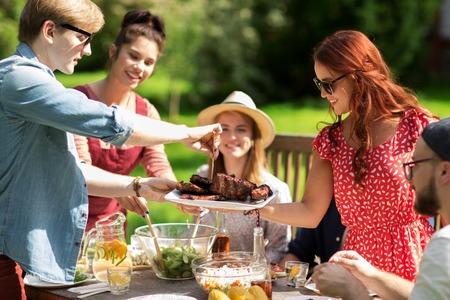 Foto de leisure, holidays, eating, people and food concept - happy friends having meat for dinner at summer garden party - Imagen libre de derechos