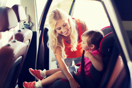 Photo for family, transport, safety, road trip and people concept - happy mother fastening child with car seat belt - Royalty Free Image