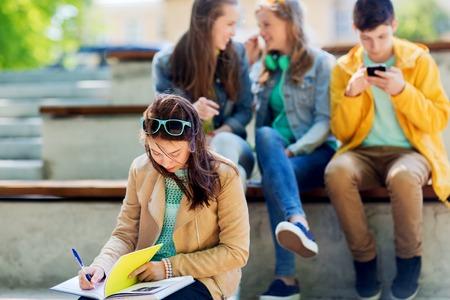 Foto de education, bullying, high school, social relations and people concept - unhappy student girl with book suffering of classmates mockery - Imagen libre de derechos