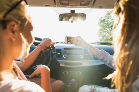 Photo pour summer vacation, holidays, travel, road trip and people concept - happy teenage girls or young women with smartphone taking selfie in car - image libre de droit