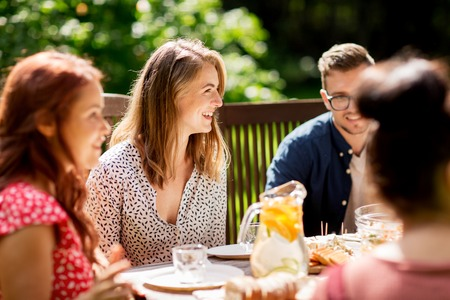 Photo pour leisure, holidays, eating, people and food concept - happy friends having dinner at summer garden party - image libre de droit