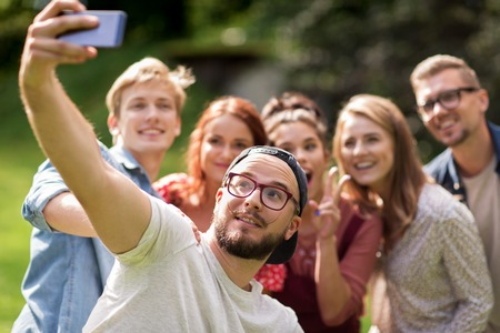 Photo for leisure, holidays, reunion, people and friendship concept - happy teenage friends taking selfie by smartphone at summer - Royalty Free Image